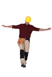 Builder balancing on one leg Royalty Free Stock Photography