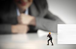 Builder with banner. Businesswoman looking at miniature of builder pulling white banner Stock Image