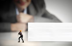 Builder with banner. Businesswoman looking at miniature of builder pulling white banner Royalty Free Stock Image