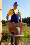 Builder with barrow. Construction worker wearing blue overall and helmet with wheel-barrow stock images