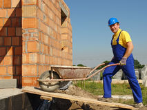 Builder with barrow. Construction worker wearing blue overall and helmet going inside unfinished brick wall building with wheel-barrow stock image