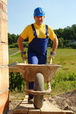 Builder with barrow. Construction worker wearing blue overall and helmet going inside unfinished brick wall building with wheel-barrow stock photo