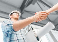 Builder with blueprint shaking partner hand. Architecture and home renovation concept - builder with blueprint shaking partner hand Stock Photos