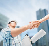 Builder with blueprint shaking partner hand. Architecture and home renovation concept - builder with blueprint shaking partner hand Stock Photo