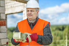 Builder with brick in the hands Stock Photo