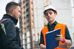 Builder briefing to achritector in hardhats with tablet pc computer outdoors Stock Photos
