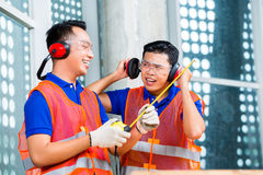Builder on building or construction site wearing. Asian Indonesian builder or craftsman and supervisor with ear or hearing protection and glasses on a tower royalty free stock photo