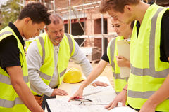 Builder On Building Site Discussing Work With Apprentice Stock Photos