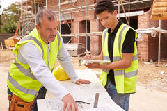 Builder On Building Site Discussing Work With Apprentice Royalty Free Stock Photos
