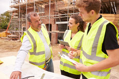 Builder On Building Site Discussing Work With Apprentices Royalty Free Stock Photos