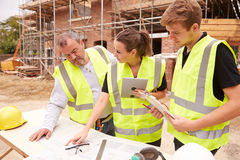 Builder On Building Site Discussing Work With Apprentices Royalty Free Stock Photo