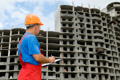 Builder and building under. One builder worker with clipboard inspecting works at construction site Royalty Free Stock Image