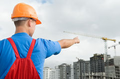 Builder and building under. Engineer worker directing up with finger to building under construction Stock Photos