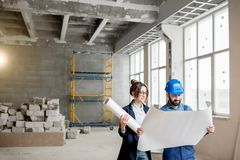 Builder with businesswoman at the construction site. Foreman expertising the structure with businesswoman holding a blueprints at the construction site indoors stock photo