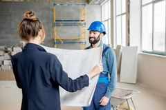 Builder with businesswoman at the construction site. Foreman expertising the structure with businesswoman holding a blueprints at the construction site indoors royalty free stock photography