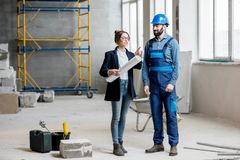 Builder with businesswoman at the construction site. Foreman expertising the structure with businesswoman holding a blueprints at the construction site indoors royalty free stock images
