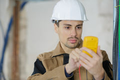 Builder calibrating device at construction site Royalty Free Stock Images