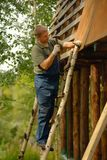 Builder or carpenter working and builds a roof Stock Image