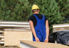 Builder carrying an insulated wall panel Royalty Free Stock Image