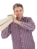 Builder carrying timber Royalty Free Stock Images
