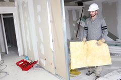 Builder carrying wall insulation royalty free stock photo