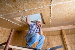 Builder on Cell Phone Inside Unfinished Home Royalty Free Stock Image