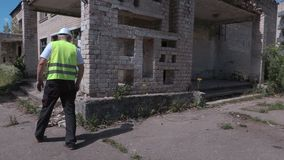 Builder checking abandoned old apartment houses stock footage