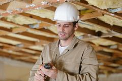 Builder checking drill stock photography