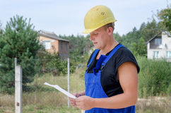 Builder checking paperwork on site Royalty Free Stock Images