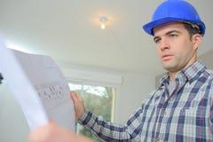 Builder checking plans Stock Photos