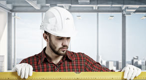 Builder checking spirit level . Mixed media Royalty Free Stock Images