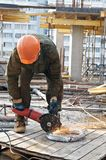 Builder with circular abrasive saw. Builder works with circular abrasive cutoff saw and sparkles at construction site stock photography