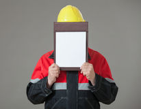 Builder closing his face with clipboard Stock Photos