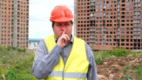 Builder on construction building site making a shushing gesture raising his finger to his lips as he asks for silence. Male builder foreman, worker or architect stock footage