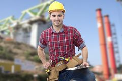 Builder construction man. Worker of the building smiling measuring with the metro Royalty Free Stock Photo
