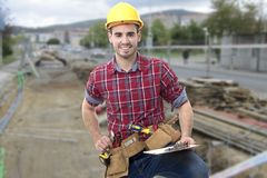 Builder construction man. Worker of the building smiling measuring with the metro Royalty Free Stock Image