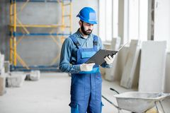 Builder at the construction site. Builder or foreman in working uniform expertising the structure standing with folder at the construction site indoors stock image