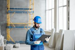 Builder at the construction site. Builder or foreman in working uniform expertising the structure standing with folder at the construction site indoors stock photo