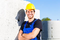 Builder of construction site with canalization project. Pride builder standing on construction or building site with sewage or canalization concrete elements Royalty Free Stock Image