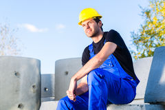 Builder of construction site with canalization project. Proud builder standing on construction or building site with sewage or canalization concrete elements Royalty Free Stock Images