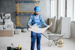 Builder at the construction site. Builder or foreman in working uniform expertising the structure standing with blueprint at the construction site indoors stock photography