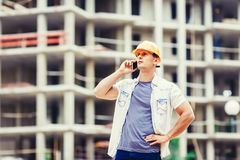 Builder at the construction site talking mobilephone. Builder engineer at the construction site talking mobilephone Royalty Free Stock Images