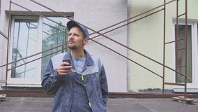 Builder or construction worker enjoying a cup of coffee near the construction, building stock footage