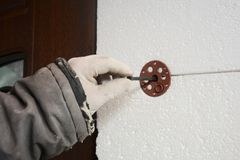 Builder contractor  installing rigid styrofoam insulation board with plastic nail for holding. Builder contractor installing rigid styrofoam insulation board royalty free stock image