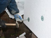 Builder contractor installing rigid styrofoam insulation board with plastic nails and hammer for house energy saving. Exterior. House wall insulation stock photo