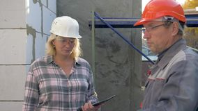 Builder and customer inspect the building under construction inside in rooms. Inside the building under construction, the builder shows and tells about the stock video