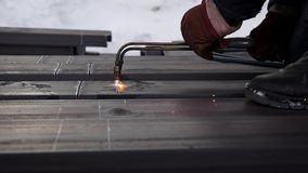 The builder cuts the metal with a special burner. Protective gloves. Splash proof stock video