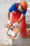 Builder at cutting curb work. Construction worker at curb stone cutting work by cut-off saw with diamond wheel Stock Photo