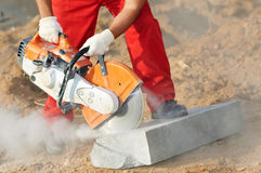 Builder at cutting curb work. Construction worker at curb stone cutting work by cut-off saw with diamond wheel Stock Images