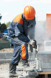 Builder at cutting curb work. Construction worker at curb stone cutting work by cut-off saw with diamond wheel Royalty Free Stock Photos